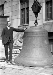 Man standing next to large bell
